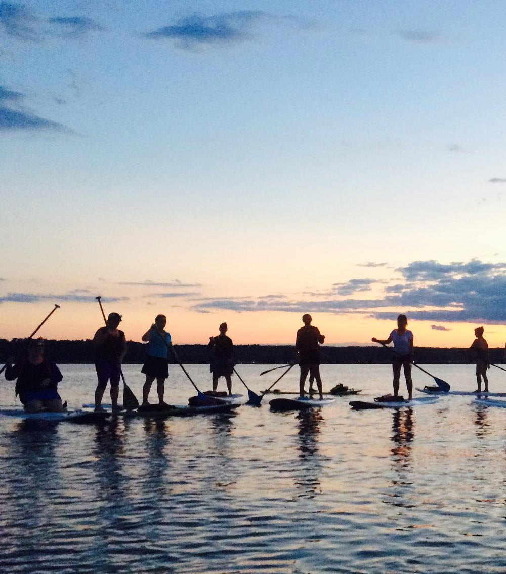 Group on paddleboats on lake during sunset